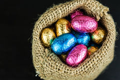 Chocolate Easter eggs in colorful foil in small jute bag. On dark background, top view stock photography