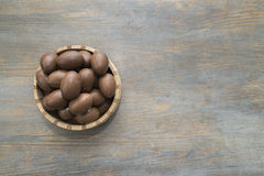 Chocolate easter eggs in a crafted wood bowl on a wooden table Royalty Free Stock Images