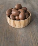 Chocolate easter eggs in a crafted wood bowl on a wooden table Stock Photos