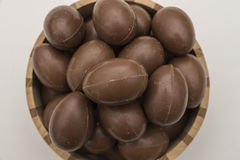 Chocolate easter eggs  in a crafted wooden bowl Stock Photos