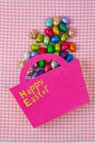 Chocolate Easter eggs falling from a pink bag Stock Image