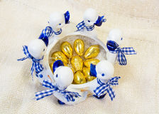 Chocolate Easter eggs in golden cover in white with blue round vase with ducks figures Stock Photo