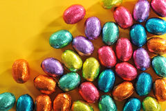 Chocolate easter eggs. Many colored chocolate easter eggs on yellow paper Stock Photos