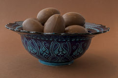 Chocolate Easter eggs in a Moroccan blue decorated bowl Royalty Free Stock Images