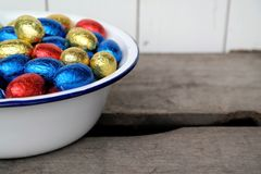 Chocolate Easter eggs, red, blue and yellow. Together in a enamel bowl, top view Royalty Free Stock Photos