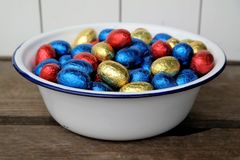 Chocolate Easter eggs, red, blue and yellow. Together in a enamel bowl, top view Stock Images