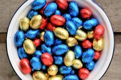 Easter chocolate eggs, colors red, blue and golden. Passover concept with wooden background, enamel bowl and top view Stock Photos