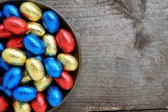 Chocolate Easter eggs, red, blue and yellow. On a wooden surface, with text space, top view Stock Photos