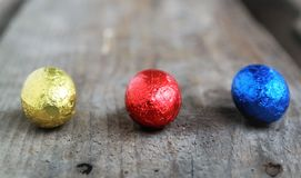 Easter chocolate eggs, three colors red, blue and golden.. Passover concept with sweets Stock Images