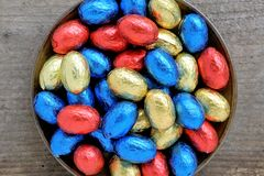 Chocolate Easter eggs, colors red, blue and golden. Passover concept with wooden background and copy space Stock Photography