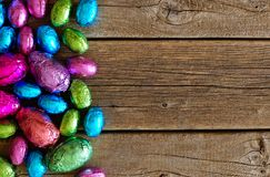 Chocolate Easter Eggs side border against rustic wood Royalty Free Stock Photos