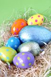 Chocolate easter eggs in straw. Chocolate Easter eggs wrapped in colorful wrap, lying in straw stock photo