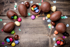 Chocolate easter eggs and sweets on wooden background. Delicious chocolate easter eggs and sweets on wooden background Royalty Free Stock Photo