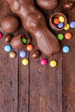 Chocolate easter eggs and sweets on wooden background Stock Images