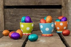 Chocolate easter eggs in three colorful egg cups stock photos