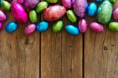 Chocolate Easter Eggs top border against rustic wood Royalty Free Stock Photos