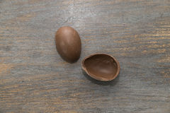 Chocolate easter eggs whole and broken on a wooden table Stock Images