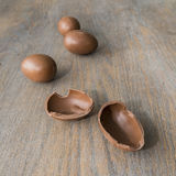 Chocolate easter eggs whole and broken on a wooden table Stock Photos