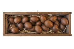 Chocolate Easter eggs in wooden crate with straw isolated Stock Images