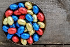 Easter chocolate eggs, colors red, blue and golden. Passover concept with wooden background and copy space Royalty Free Stock Images