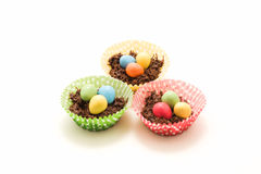 Chocolate Easter Nests and Eggs. Chocolate Easter nests with little easter eggs inside surrounded by multicoloured cases Royalty Free Stock Photos