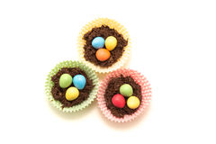 Chocolate Easter Nests and Eggs. Chocolate Easter nests with little easter eggs inside surrounded by multicoloured cases Royalty Free Stock Photography
