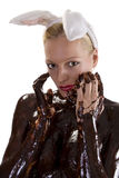 Chocolate easter white. Attractive naked blond girl covered in chocolate wearing bunny ears Royalty Free Stock Photos