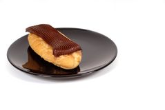 Chocolate eclair on black plate. Delicious chocolate eclair on black plate Stock Photos
