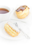 Chocolate eclair dessert powdered sugar. Filled custard on a white plate with an elegant fork and cup of tea Stock Photos