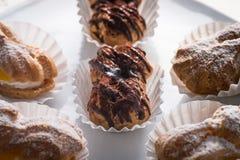 Chocolate Eclairs and Cream Puffs. Profiteroles or chocolate eclairs or cream puffs stock photo