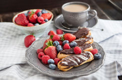 Chocolate eclairs with fresh berries Stock Photography