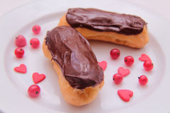 Chocolate eclairs on plate on white background sprinkled with red currant berries and hearts Stock Photo