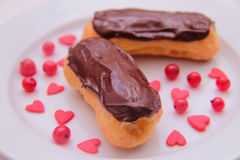 Chocolate eclairs on plate on white background sprinkled with red currant berries and hearts Royalty Free Stock Photography