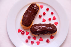 Chocolate eclairs on plate on white background sprinkled with red currant berries and hearts Royalty Free Stock Photos