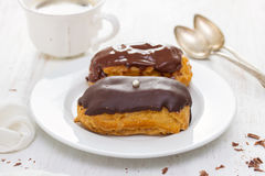 Chocolate eclairs on white dish on wooden background Stock Photo