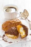 Chocolate eclairs on white dish on wooden background Stock Photos