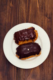 Chocolate eclairs on white dish on wooden background Royalty Free Stock Image