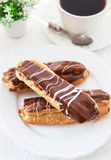 Chocolate eclairs on white plate Royalty Free Stock Photo