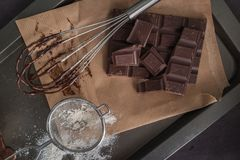 Chocolate on egg beater and chocolate parts on wooden table top Royalty Free Stock Photos