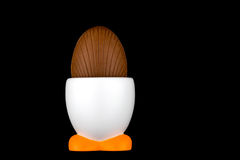 Chocolate Egg in Egg Cup on Black Background Stock Image