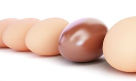 Chocolate egg and egg row. On a white background Royalty Free Stock Images