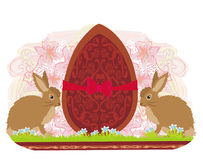 Chocolate egg with red bow and two beautiful rabbits Royalty Free Stock Photo