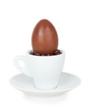 Chocolate egg on a white cup and saucer Royalty Free Stock Photo
