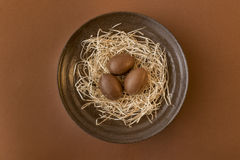 Chocolate eggs in a crafted bowl on a brown background Stock Image