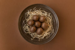 Chocolate eggs in a crafted bowl on a brown background Royalty Free Stock Photos