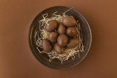 Chocolate eggs in a crafted bowl on a brown background Stock Photography