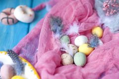 Chocolate eggs of different colors. Pink background and feathers. Easter. Spring decor. royalty free stock images