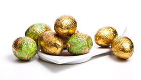 Chocolate eggs in foil. On white plate, isolated on white background Royalty Free Stock Images