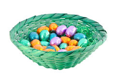Chocolate eggs. Isolated colorful chocolate eggs in a green basket Stock Images