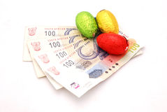 Chocolate eggs on Rands. Four one hundred notes of South African Rand money with colorful wrapped chocolate Easter eggs. Image isolated on white studio Stock Images